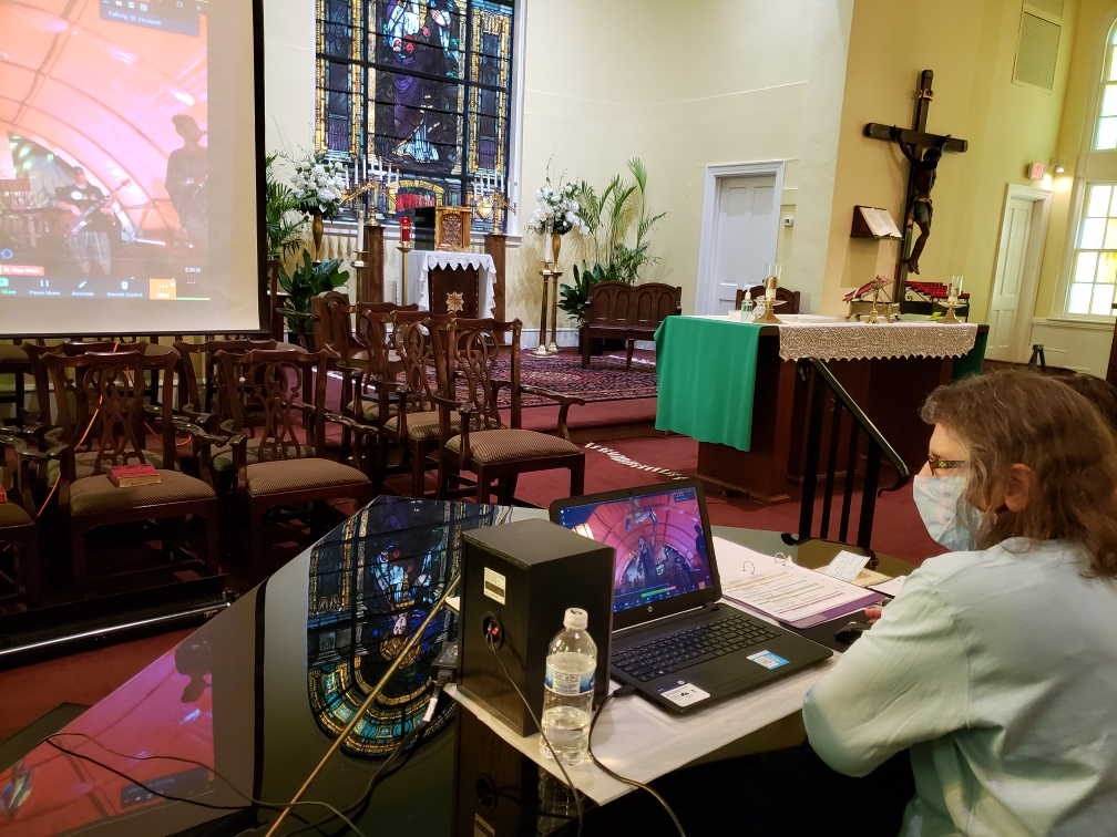 A woman looking at a laptop on a table with the same image projected on a big screen at the front of the church.