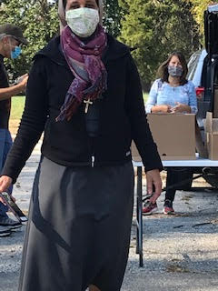A woman wearing a mask in the parking lot of a church