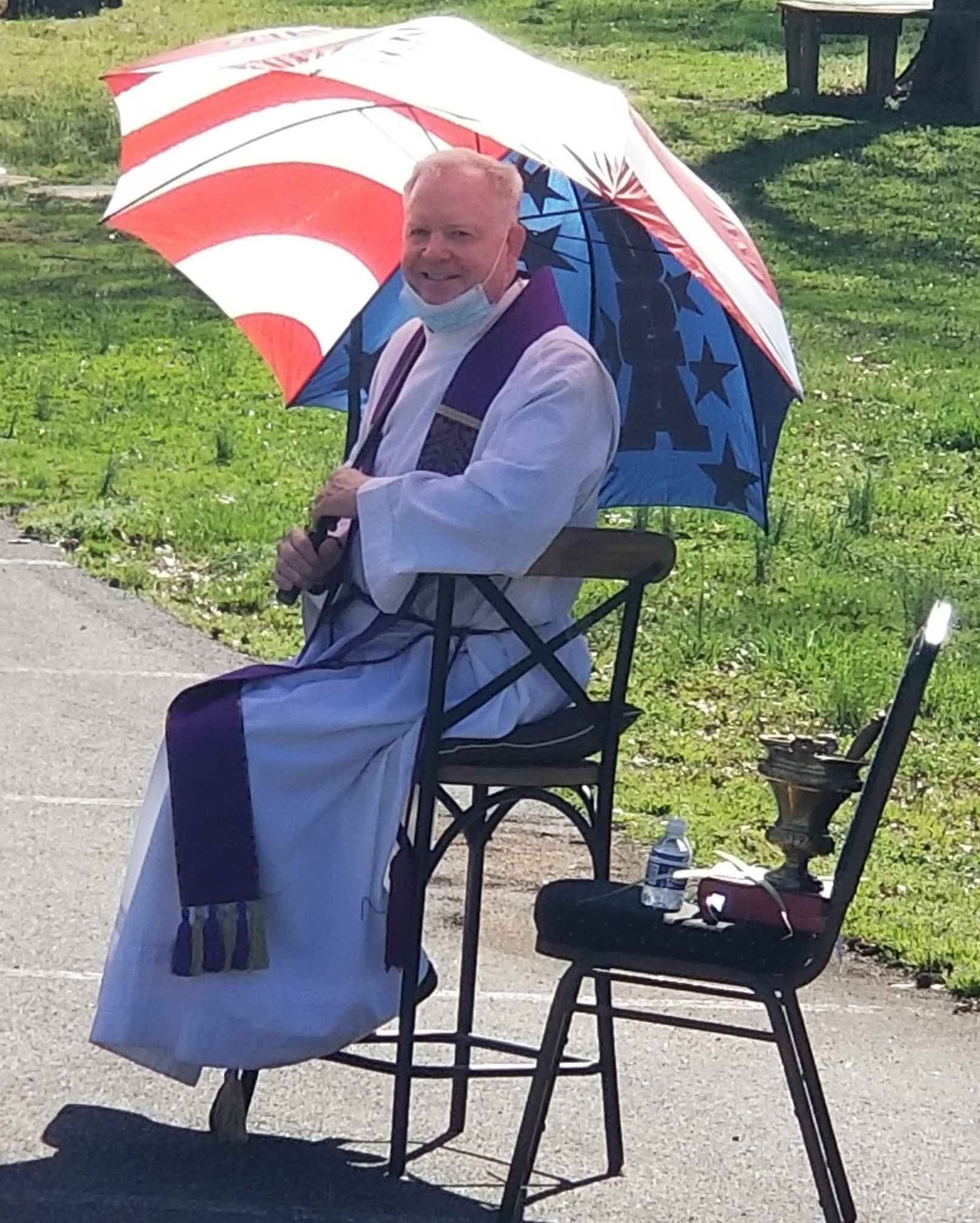 A priest sitting in a chair under an umbrella in a parking lot